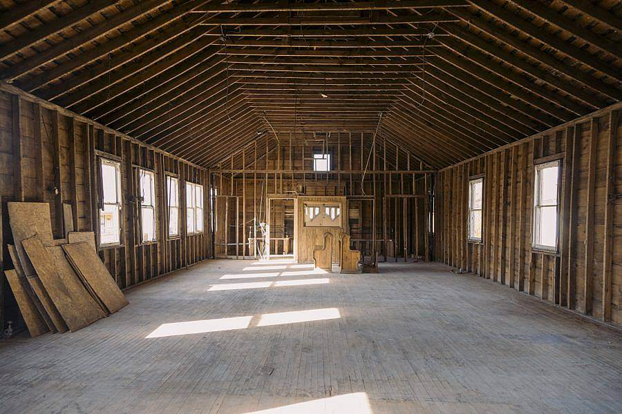 Image description: A stripped down all wooden interior of a building is displayed. Natural light pour in through the windows.