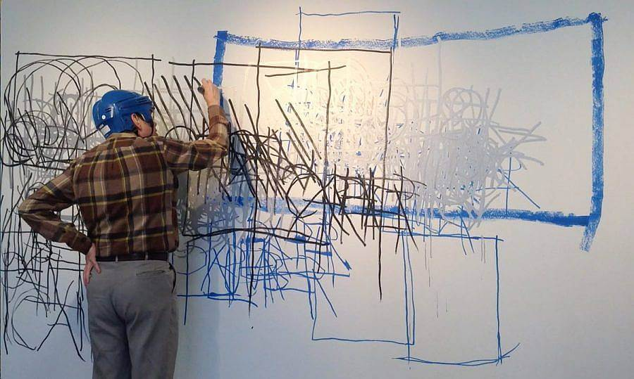 Image description: Artist Dan Miller wears a blue protect helmet and an olive green plaid shirt. He is using a black marker to make marks on a large white surface.