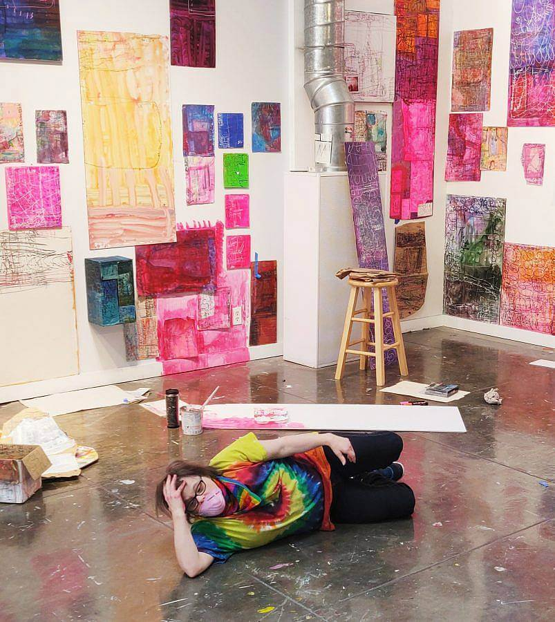 Image description: Artist Nicole Storm lays on the floor with a light pink mask over her face. Her colorful artwork covers the walls on both sides. There is pink coloration on the walls painted or drawn on.