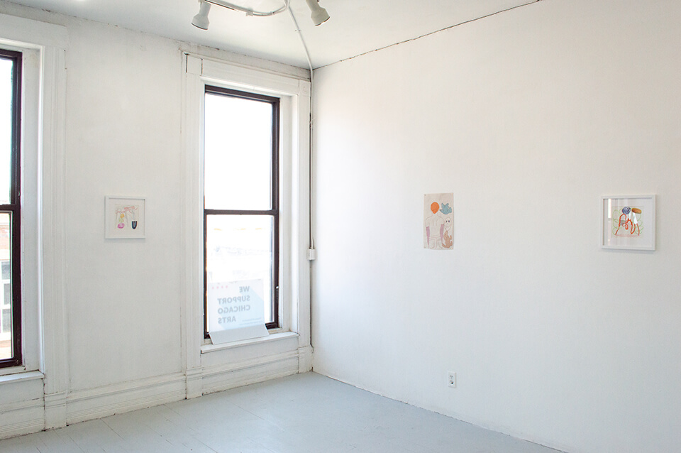 Image Description: This is an installation shot of the corner of the gallery. To the left of the window is