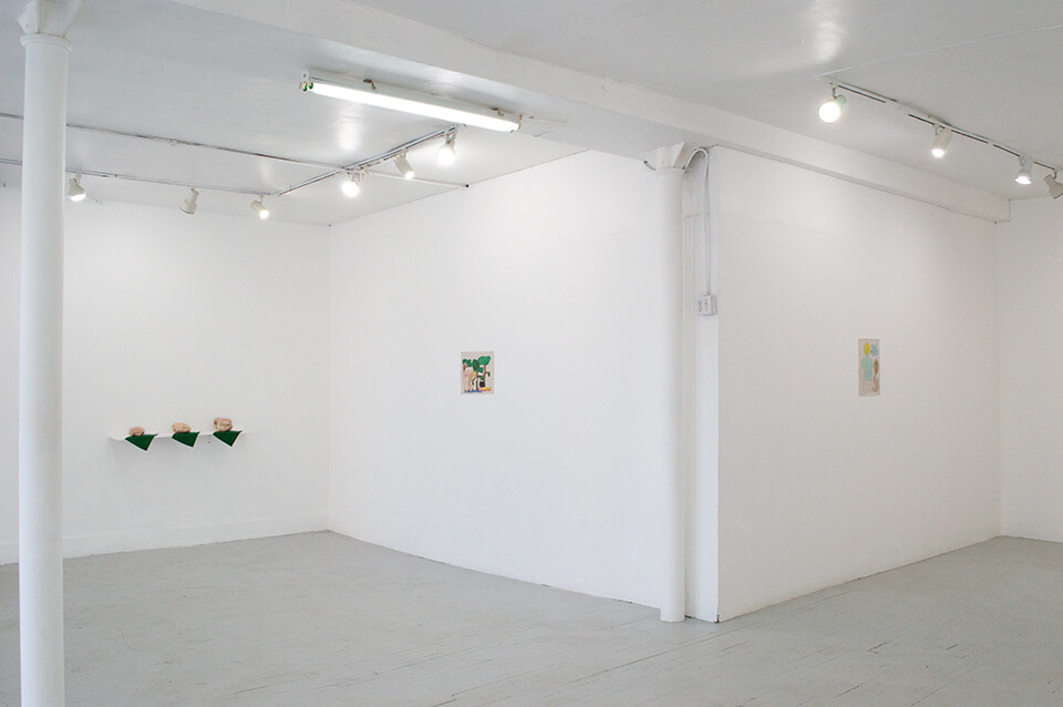 Image Description: This is an installation shot of a corner of the gallery. On the left side is