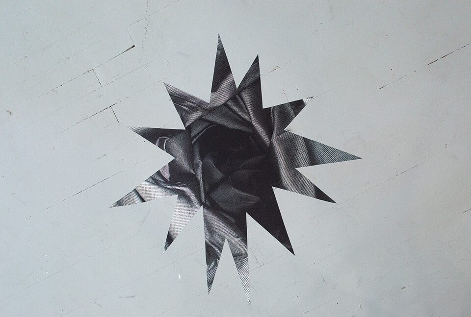 Image Description: This is a sticker of a multi-pointed star attached to the floor. The stick appears to be cut from an abstract black and white image.