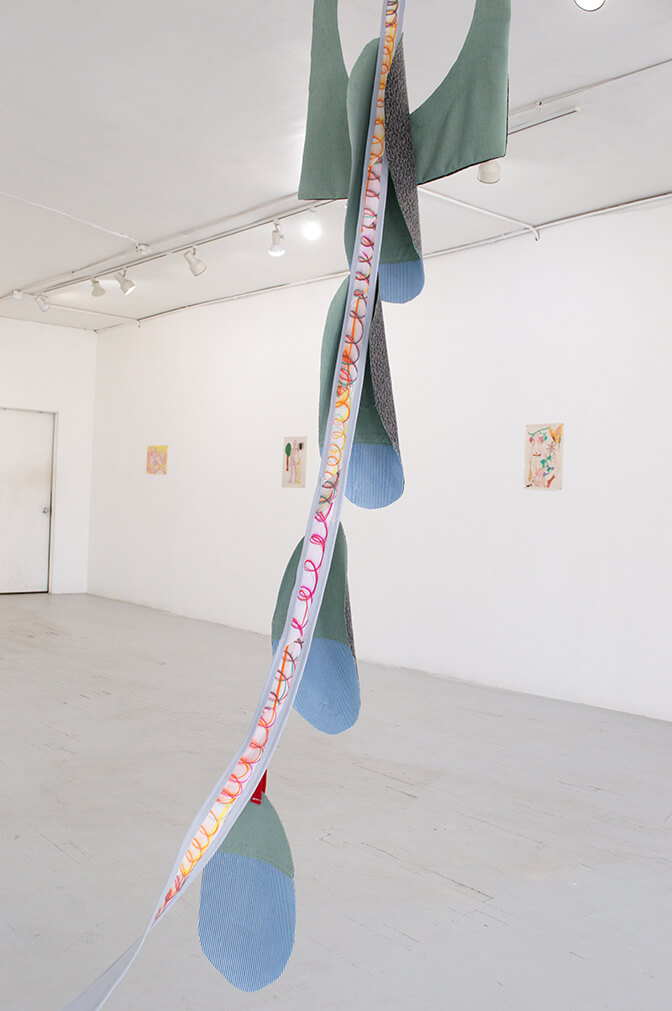 Image Description: A strip of fabric is hanging from the ceiling. One side is light blue and curves over the edges. A chain of multi-colored loops is drawn in crayon on the other side and there are several oval-shaped sheets of fabric hung at equidistance from the strip.