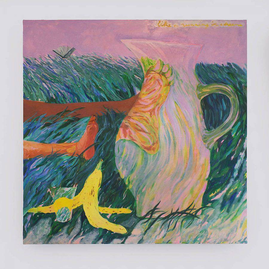 A banana peel and water pitcher sit on a grassy landscape. Behind the pitcher are a figures feet lying in the grass. The. sky is a soft pink, the grass of blues and greens. The figures foot becomes magnified behind the water pitcher.