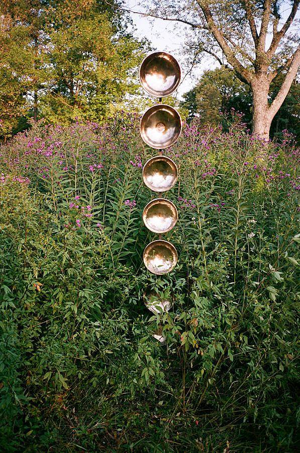 Image Description: Standing amongst a big flowering bush is a tall stack of gold singing bowls. The center of the bowls are facing the viewer.