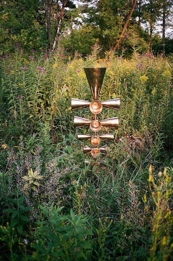 Image Description: Standing amongst a dense mix of wild plants is a stack of golden bells. On each level, there are cone-shaped bells on all four sides and the bells progressively get bigger towards the top. The largest bell is stacked on top.