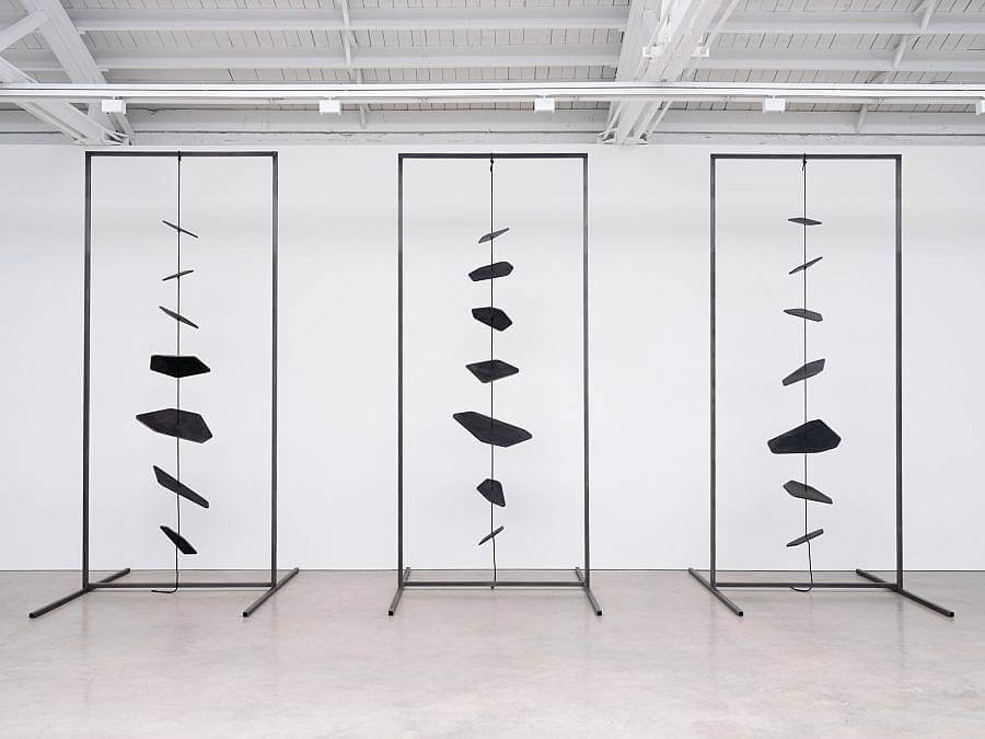 Image Description: Facing the viewer are three metal rectangular free-standing frames. Stretched through the center of each is a black rope with seven spinning black metal shapes of various sizes.