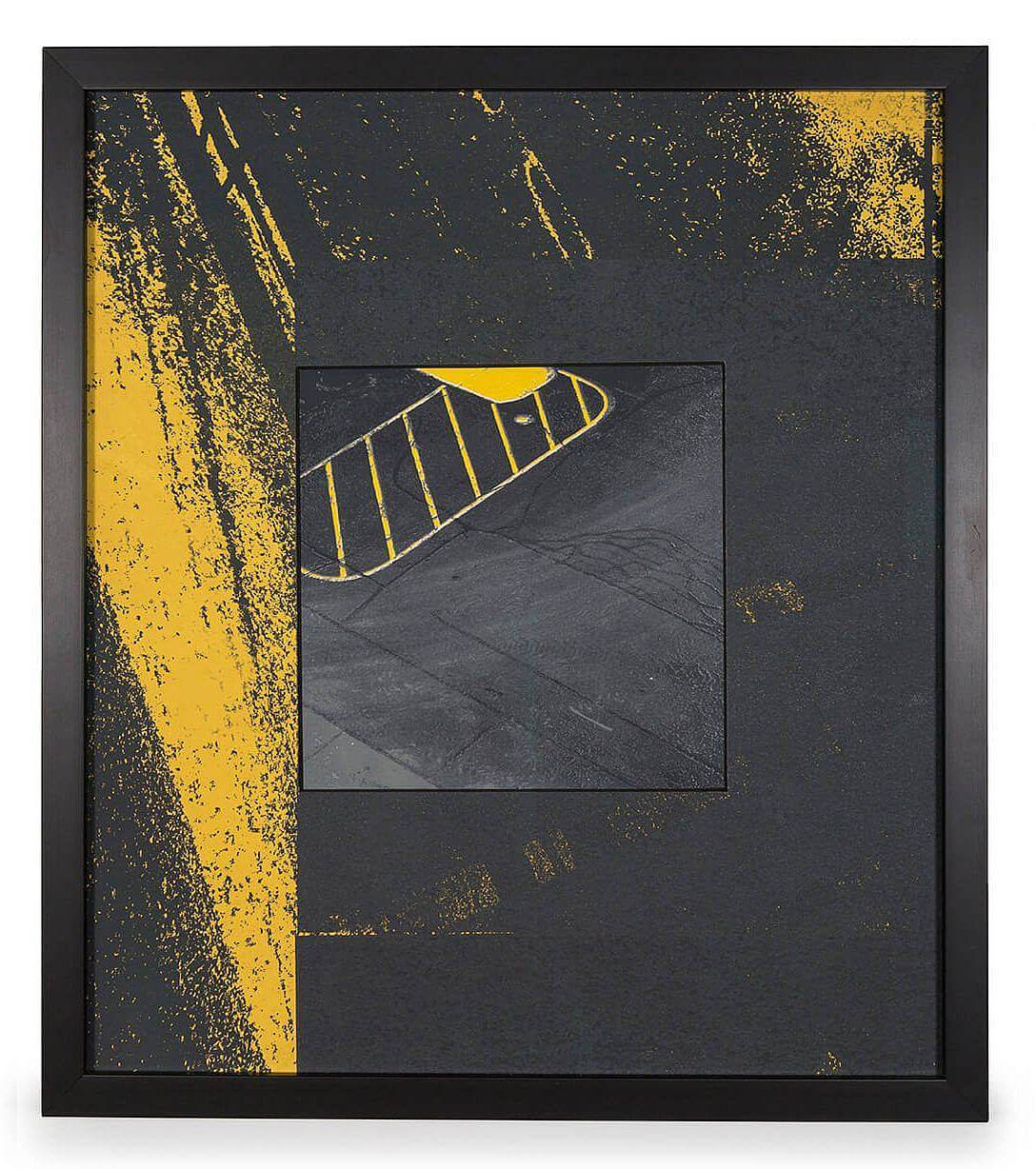 Image Description: There is a thick border around the image depicting a close-up image of black asphalt with yellow markings. The image in the center of the piece is a birds-eye view of an asphalt parking lost with a yellow outline of an oval with diagonal stripes going across.