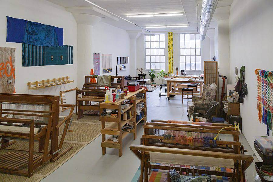 Image Description: This is an image of a communal studio space with multiple looms and other tools for fiber work. There are large windows at the far end of the room and various weavings hanging on the wall.
