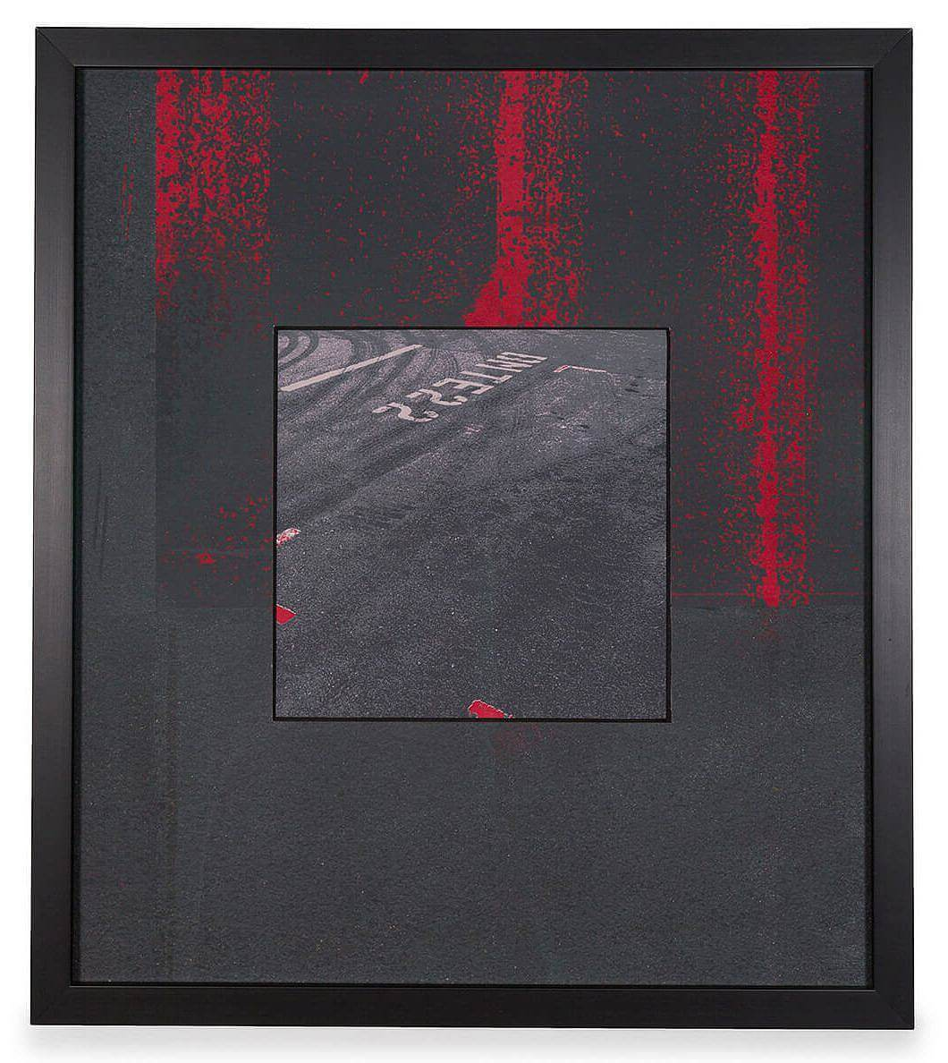 Image Description: There is a square image in the center of the piece that depicts a birds-eye view of an asphalt parking lot or street. The image is surrounded by a thick black border with bright red vertical streaks coming down from the top.