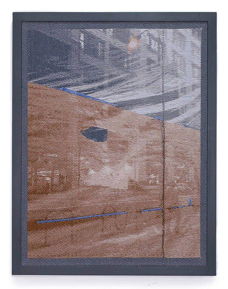 Image Description: This is a vertical rectangular weaving in a dark blue-grey frame. The weaving depicts a street scene with a tall office building, bike racks, and a street lamp. The top of the image is down in shades of grey and the bottom is in variations of an orange-brown.