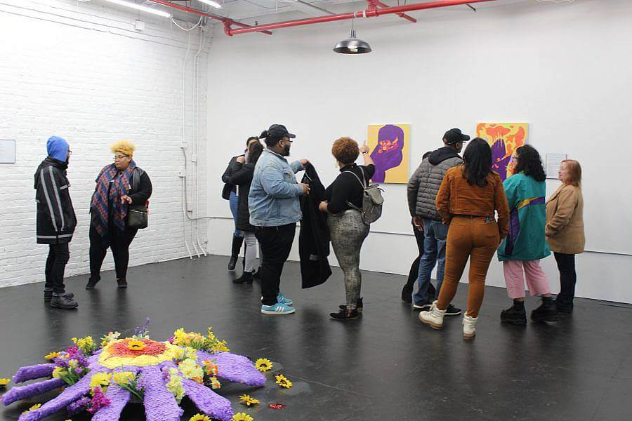 Image description: A group of eleven people are in an exhibition space. To the left a large purple and yellow pinata flower is placed on the ground.