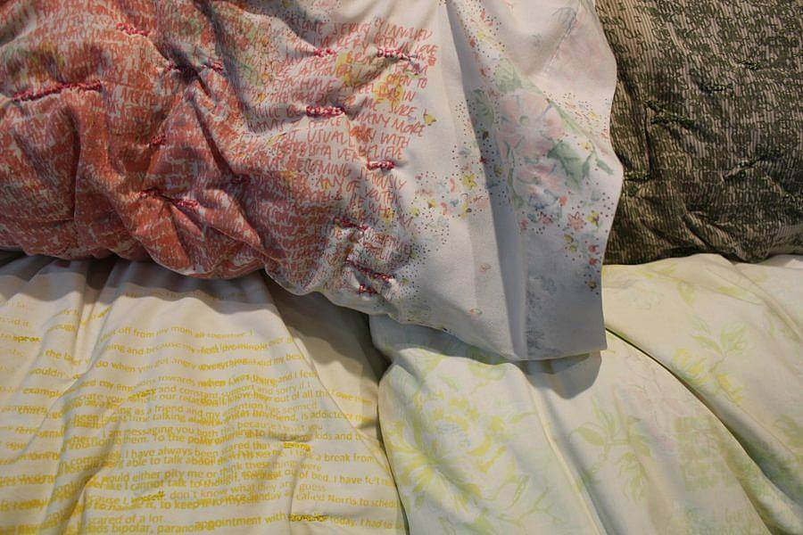 Image description: Four pillow cases are displayed. The one most centered has orange layered writing all over it To its left a soft brown has green writing layered on it. Below the white pillowcase is one with mustard yellow writing. The pillowcase beneath that has a soft green and lilac floral pattern.