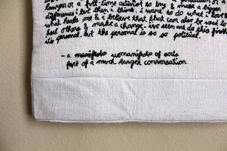 """Image description: black text is embroidered on a fabric in cursive. Certain parts can be made out, like """" The personal is so so political,"""" it is titled """" - a manifest womanifesto of sort part of a much longer conversation"""""""