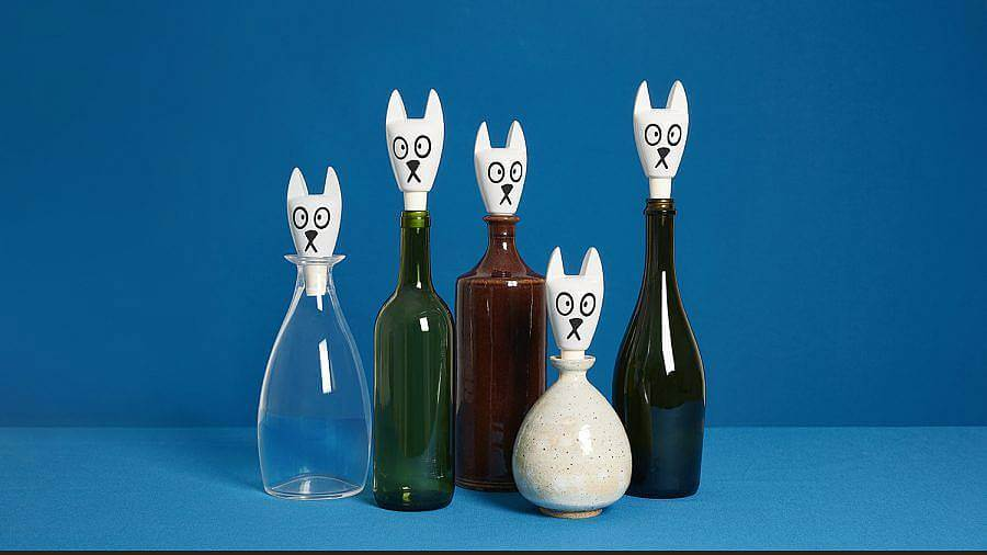 Image description: A series of five vessels are displayed in front of a blue background. The vessels are all glass, except for the fourth from the left which is ceramic. They all have white cat head bottle stoppers in them. The bottle stopper is fit with pointy cat ears, big eyes, and a small mouth.