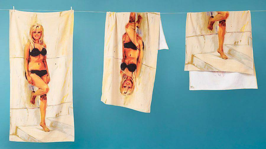 Image description: A series of three towels hang on a line in front of a yellow blue background. The towels feature an illustration of a blonde woman leaning up against a stone wall wearing a black bikini.