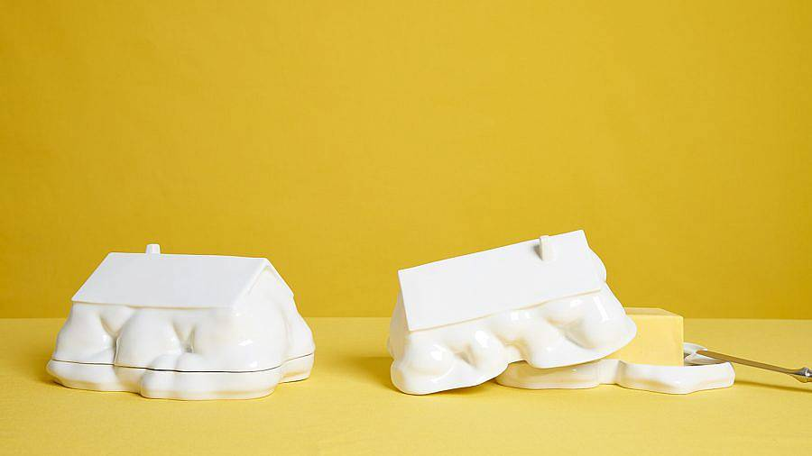 Image description: Two butter dishes are placed on a mustard yellow table in front of a similarly colored background. The butter dishes are shaped like homes that have natural formations have grown around them. The bottom half of their forms appears organic. The right butter dish is left partially ajar to display a stick of butter sticking out.