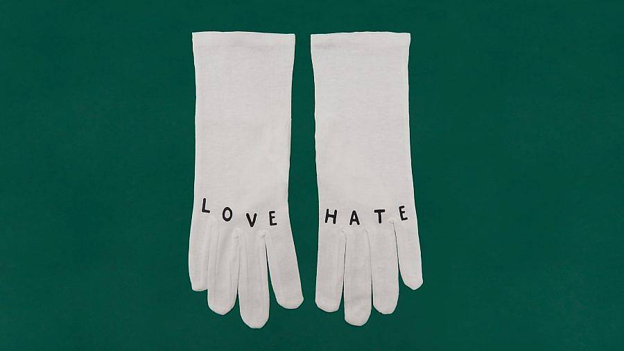 """Image description: Two white gloves are displayed against a green background. The glove on the left reads """"LOVE"""" on the knuckles, the one on the right reads """" HATE""""."""
