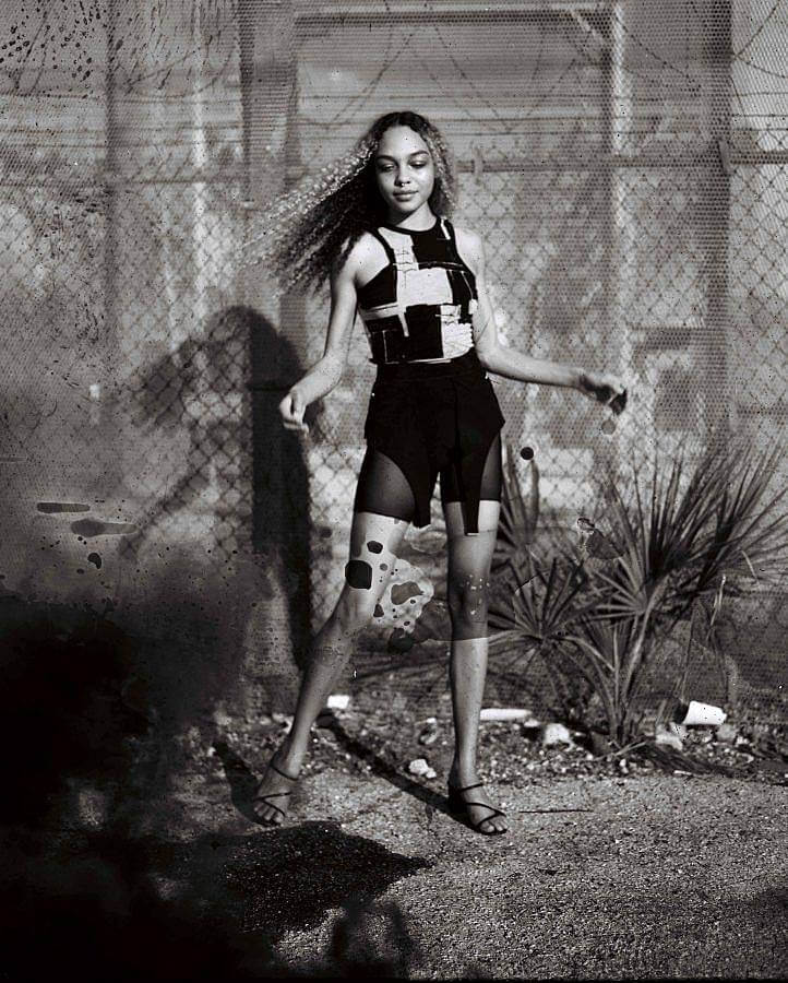 Image Description: The model is facing the camera wearing the MODU brick top without the sleeves. They are also waring high waisted shorts clipped to a pair of tights with holes in them that end after the ankles. The photograph is in black and white.