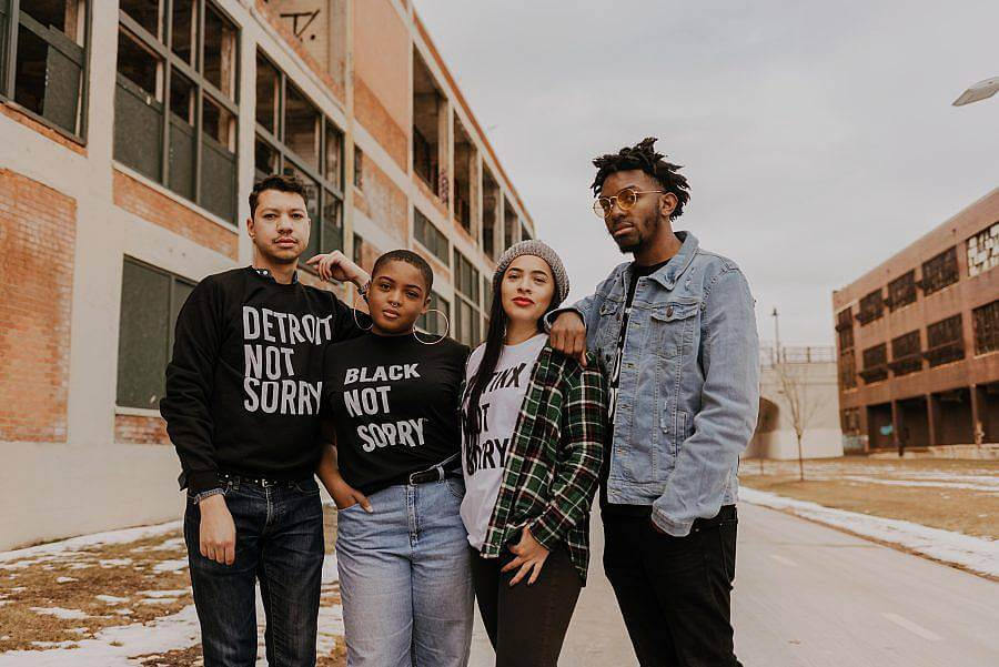 "Image Description: There are four people standing together in front of a set of buildings facing the camera. Three are wearing Not Sorry Goods shirts that say ""Detroit Not Sorry"", ""Black Not Sorry"", and ""Latinx Not Sorry""."