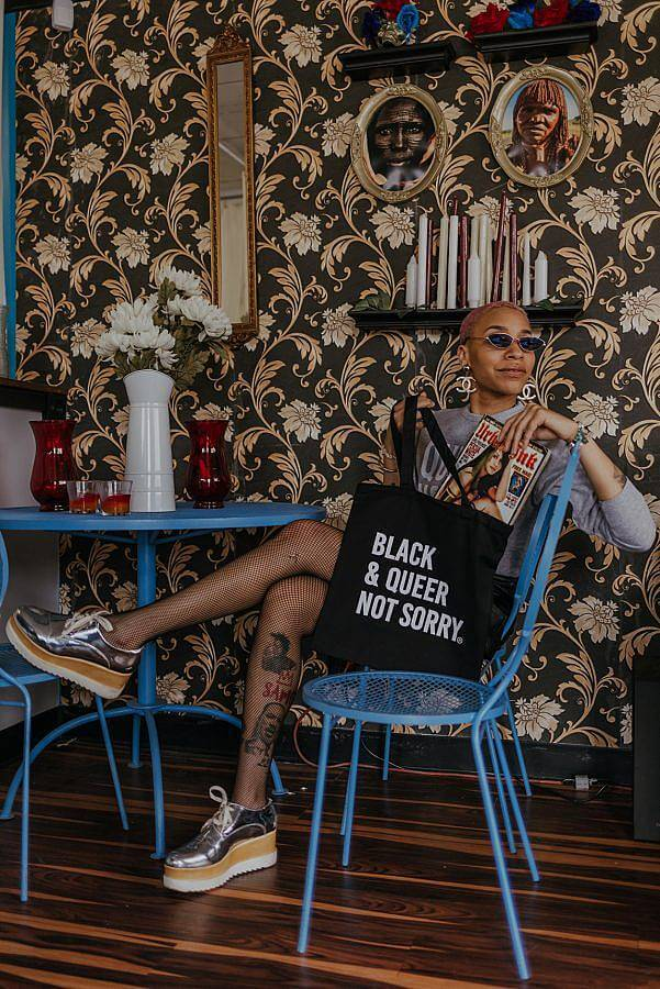 Image Descriptions: There is a figure sitting in a blue metal chain pulling a magazine out a black tote bag. The tote bag says Black & Queer Not Sorry on it and the person is wearing sunglasses and has their legs crossed. There is a floral black and gold wall-paper in the background.
