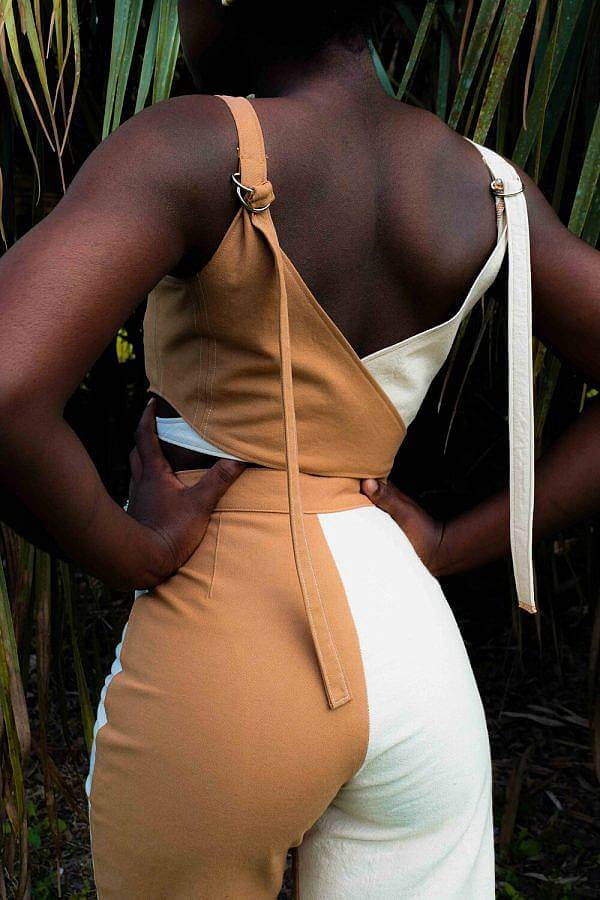 Image Description: This is an image of a model standing with their back to the camera and their hands on their hips. wearing a matching tank top and high waisted pants. One half of each garment is tan and the other half is terracotta.