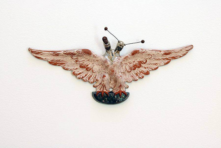 Image Description: This is a ceramic wall piece of a bird with it's wings outstretched with two silver human heads. The body is a terracotta orange with a dusty white on top. The two heads are both wearing black mouth coverings and one has a set of black antennas.