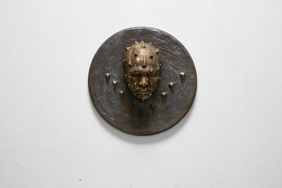 """Image description: This is a circular wall piece with a face protruding from the center. The face is looking down and is covered with spikes. There are spikes on the plaque in a """"V"""" formation under the face as well."""