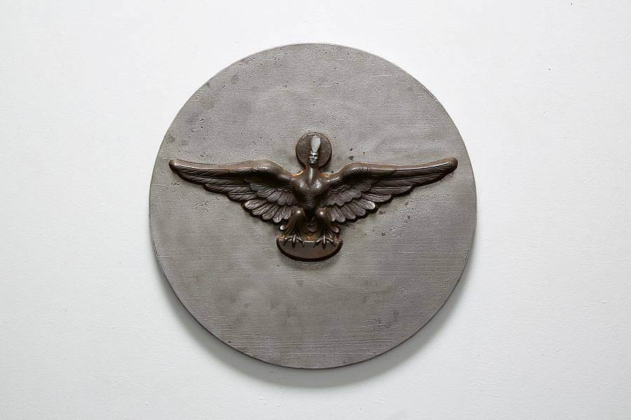 Image Description: This is a circular wall piece with a bird with a small human head embossed in the center. The wings are outstretched and the bird is perched on a half oval. There is a small circle around the human head and the head is wearing a tall narrow hat.