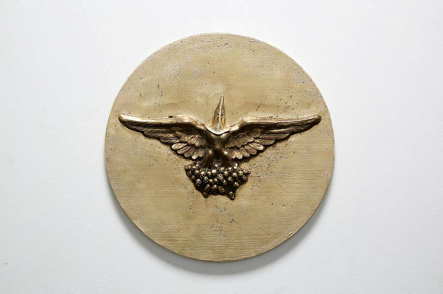 Image Description: This is a circular wall piece with a figure with outstretched bird wings embossed into the center. The man appears to be standing on a mass of small balls and is wearing a Ku Klux Klan hood over his head.