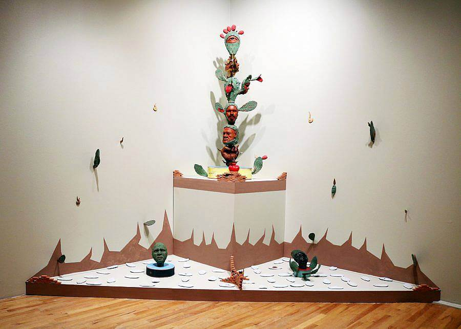 Image Description: This is an installation centered in the corner of a room. On a triangular pedestal, there is a wall cacti with red faces on the leaves. Surrounding it, on a slightly raised platform near the floor, are two green faces in cactus forms and intersecting sets of terracotta stairs.