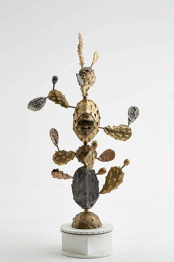 Image Description: This is a metal sculpture of a cactus in metallic gold and silver tones. There are two faces protruding from the cactus. The face facing the viewer is wearing aviator sunglasses and has a mustache.
