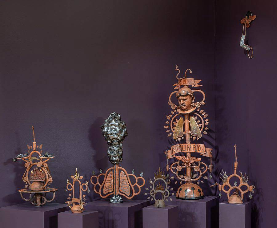 Image Description: This a collection of ceramic pieces on pedestals in a dark purple room. The pieces of varying heights and a visually complex, incorporating loops, lungs, leaves, flames, and more. They are all a terracotta orange with touches of black and a metallic dark green.