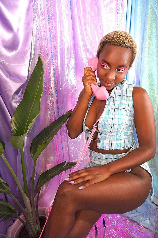 Image description: A dark-skinned black woman with short blonde hair wears a baby blue plaid two piece. The top is a vest that ties in the middle and the bottom is straight mini skirt with a slit down the leg. She holds a pink phone in front of a satin purple backdrop. A bird of paradise is next to her. She is sitting on an a clear acrylic stool.