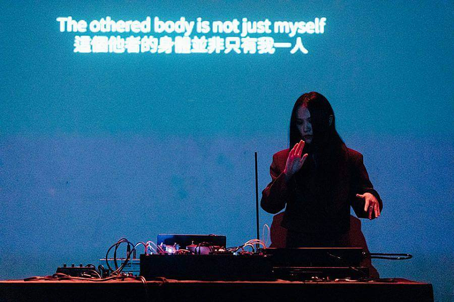 """Image description: In this photograph Yilei performs live at Rich Mix. In the photo they are standing behind some electronic music equipment and behind them the words """"The bothered body is not just myself"""" are projected in white onto a deep blue backdrop. Yilei is illuminated in red light."""