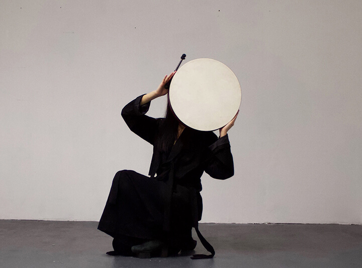 Image description: This image is a photograph of Li Yilei. They are pictured squatting in a room with white walls and concrete floors. They are holding a large, round, beige drum in front of their face. They are dressed in all black.