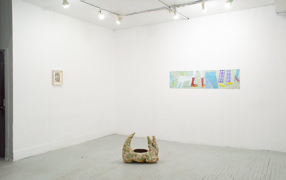 Image description: This is an installation view of the exhibition. There is a sculpture on the floor that resembles and alligator with a grill on its back. There is a small framed work hung vertically. and on the opposing wall there is a long painting hung horizontally.