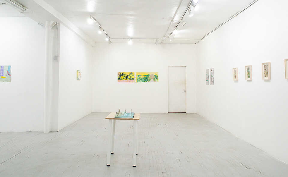 Image description: This is an installation view of the exhibition. It features three walls of the gallery and a sculpture on top of a table. There are several works on paper and paintings on the walls.
