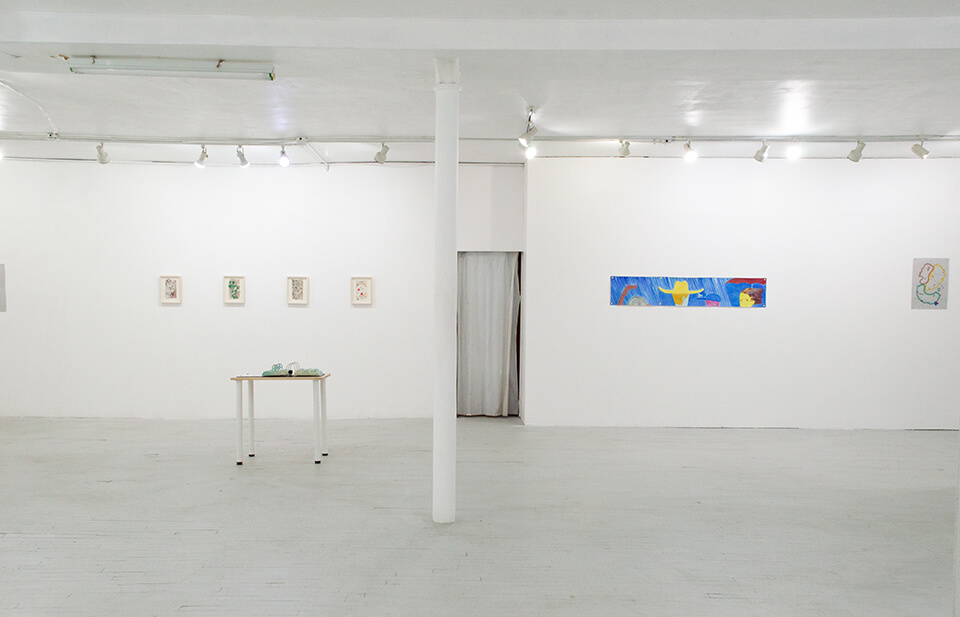 Image description: This is an installation view of the exhibition. There are several small, rectangular works that are framed and hung side by side on the left wall. On the right wall there is a long painting hung horizontally and the is a sculpture that resembles the shape of a three ring binder on a table.