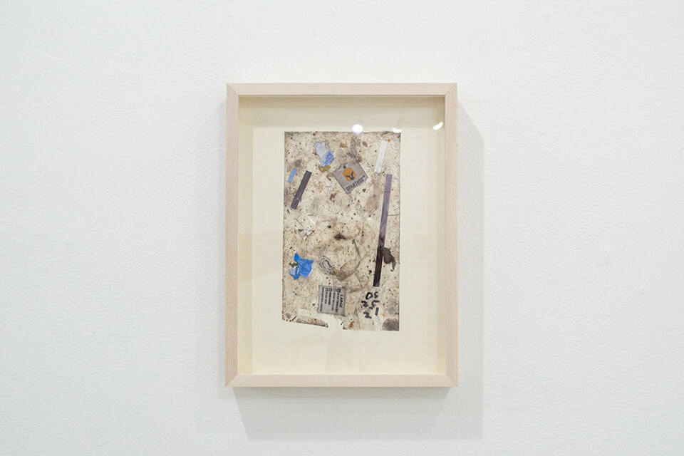 Image description: This is a work by Justin Nalley titled; Untitled (Studio Floor 052521). This work resembles a collection of dust and debris that is stuck to a large piece of tape and is framed in a wooden, recessed, rectangular frame.