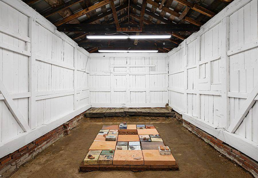 Image Description: This is an installation shot of Bad Water's most recent exhibition. On the floor is a large rectangular platform with various square tiles made of different types of clay layered on top. There are also various stones of different colors and sizes scattered on top. This sculpture is in a small room with white wooden walls reminiscent of a barn interior.