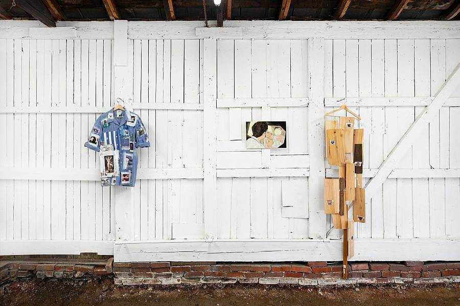 Image Description: Two objects on wooden hangers hang against the white wooden walls of the gallery. One is a blue button-up short-sleeved shirt with photographs attached all over. The other hanging object is a set of thin wooden sheets of different heights, lengths, and widths. In between both hanging object is a small painting of a figure looking in a mirror.