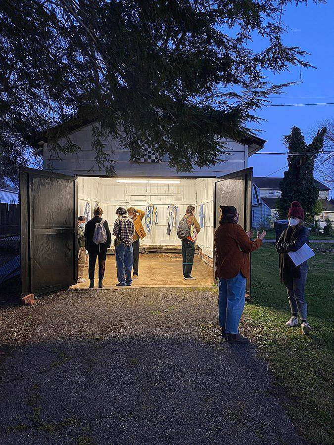 Image Description: This is a photograph of the opening at the gallery in early event. There are various people looking at the work inside the gallery and two people having a discussion outside. All visitors are masked.