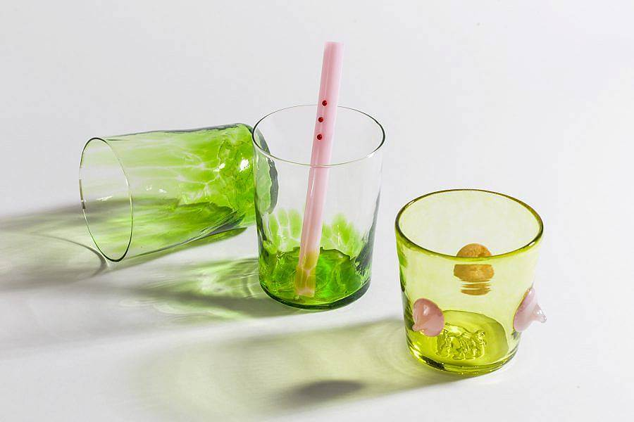 Image Description: There are three glasses in the photograph; the two to the left are transparent with bright green speckled on the bottom. The cup to the right is a more yellow-toned green with three light pink three dimensional dots along the side. There is a pink glass straw in the center cup with three red three dimensional dots lined up at the top.
