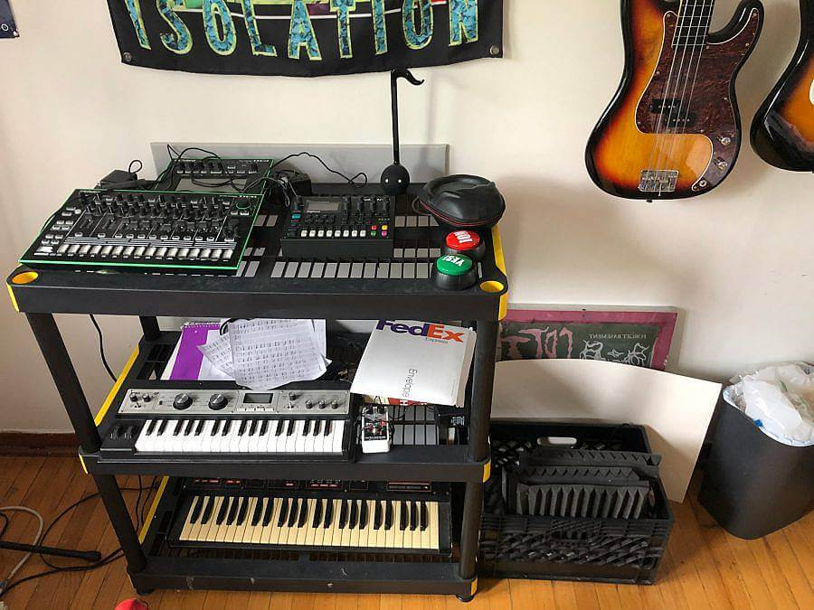 """image description: This image features Forget Basement's workspace and musical equipment. There is a table with several panels of knobs and switches, below there are various keyboards accompanied by papers and wires. On the wall there is a poster with the work """"isolation"""" printed in green next to two guitars hanging on the wall."""
