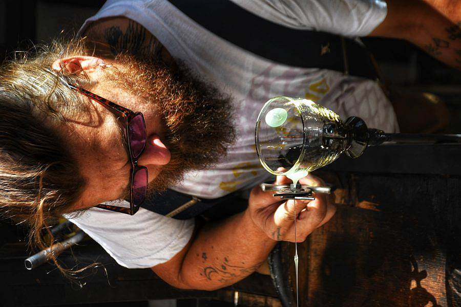 Image Description: This is a photographed of founder Eli working on a glass. He is leaning down to cut a thin stream of glass that form a three dimensional dot on a cup. He is wearing sunglasses.