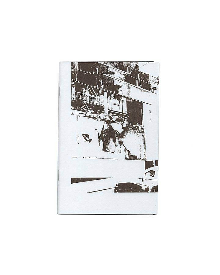 image description: This is a photograph of a book published by Soup Press in 2019. The cover of the book is pictured it has a very high contrast photograph screen printed in brown ink onto white paper. The image features an obscured window and shelving units.