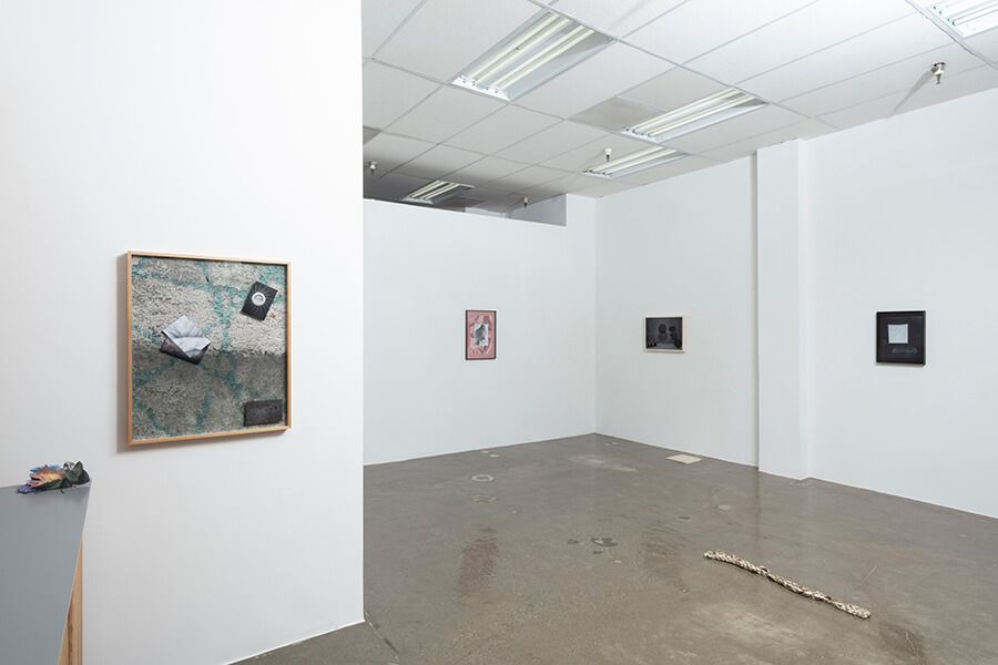 image description: This image is an installation view of After Afterlife at the Fulcrum. The gallery has three walls visible, there. are several framed, rectangular works hung on each wall. There is also a linear sculpture that resmebles a stick that is on the floor. The gallery has white walls, a paneled ceiling, and cement floors.