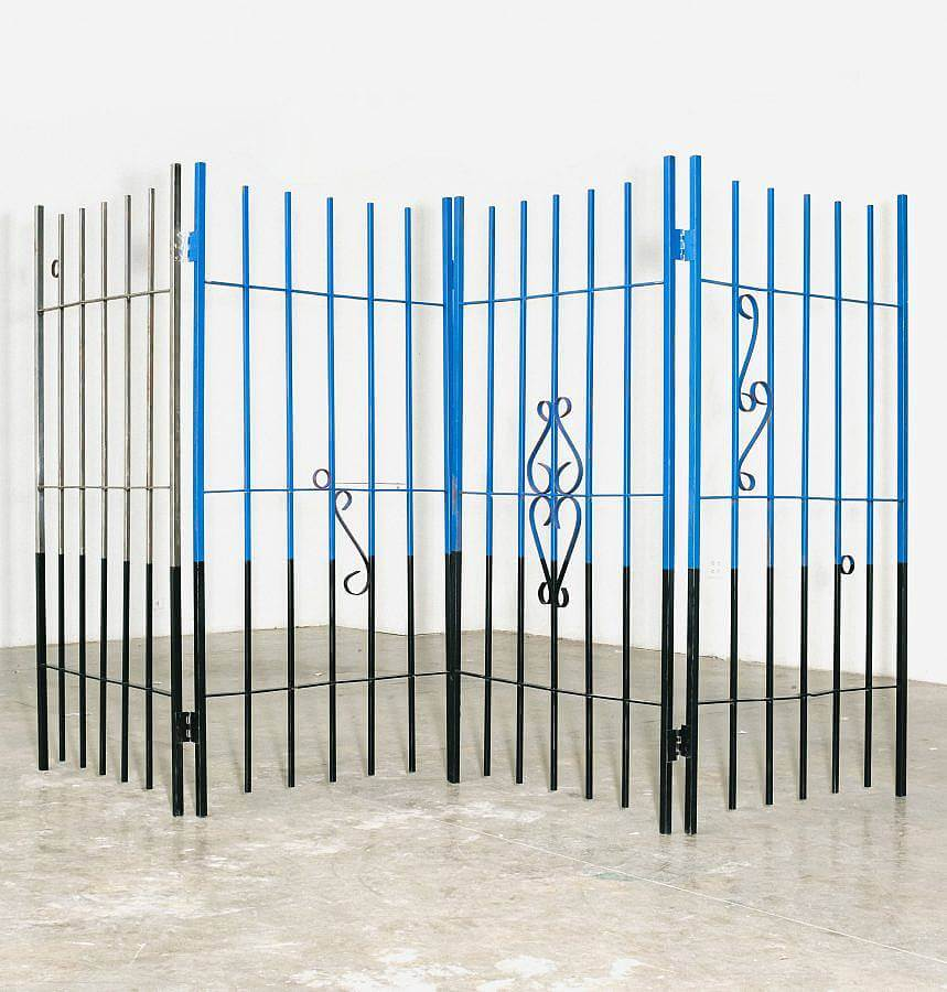 Image Description: This is a large free-standing sheet of wrought iron fencing. It is set up in a zig zag formation and there are various common fencing symbols placed throughout the piece. The top of the piece is painted blue and grey with the bottom painted black.