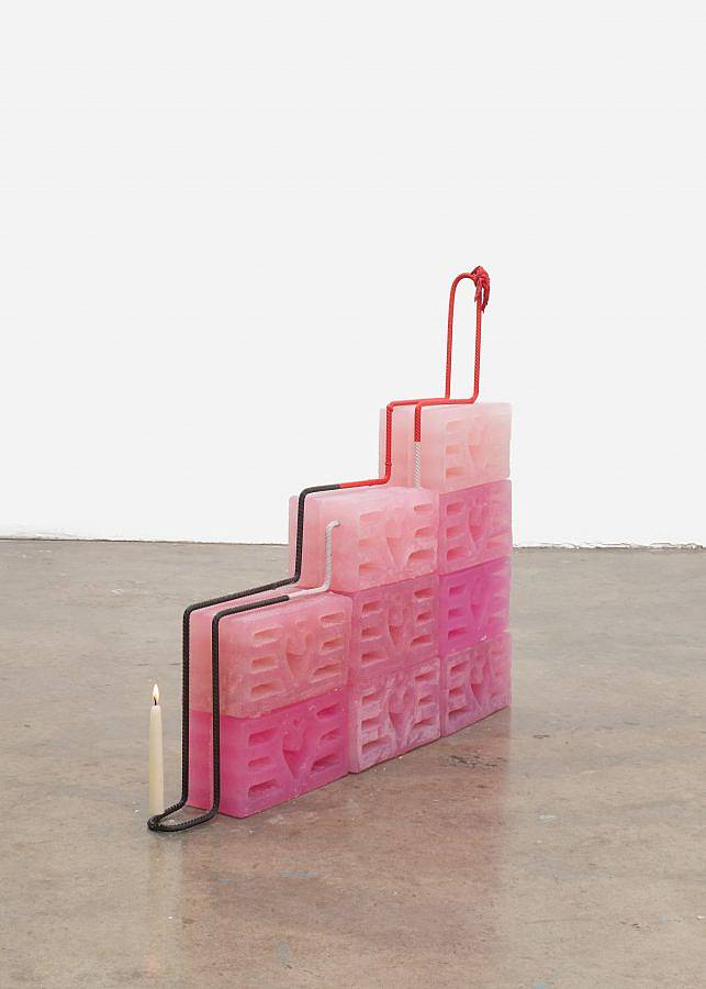 Image Description: There are a set of nine breeze blocks cast in pink soap assembled like a staircase. Steel rebar runs over and through the blocks stacked on top holding everything together. There is a lit tapered candle balanced on the rebar at the bottom of the staircase and there are hearts in the design of the breeze blocks.